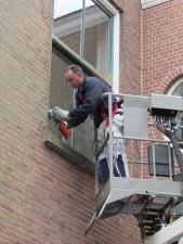 De schilders schuren dubieuze plekken machinaal volledig kaal vanuit hoogwerkers
