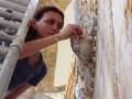 Een monnikenwerk, de reiniging van de sterk vervuilde gedetailleerde ornamenten door een gumtechniek