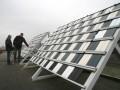 Op het dak geeft Bert Harsevoort uitleg aan bas Burema bij de expositierekken met de honderden plankjes
