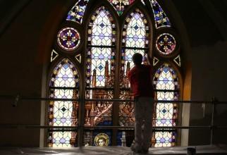 Een schilder brengt rond een glas-in-lood-raam een okergeel kozijneffect op de muur aan.
