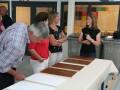 De vertegenwoordigers van de verffabrieken en verfgrondstofleveranciers bekijken de proefpanelen in Schilder^sCool Nuenen.